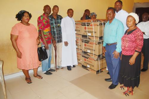Rev. Ezekiel igbokwu of St Marks church, his assitance, some members with a cross section of theb items donated by the Adure and Onyina Obioha Foundation.