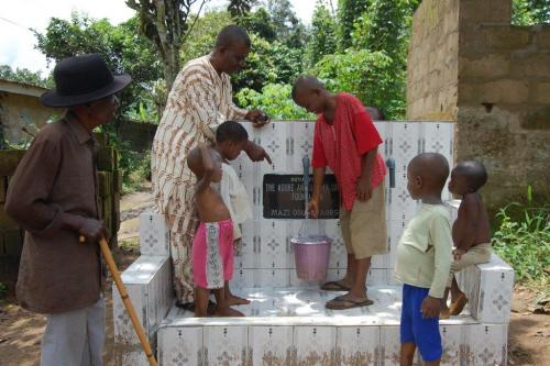 Mazi Osu's grandkids fetching water from the new borehole as Mr. Boniface Okorie watches