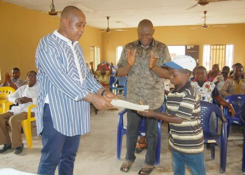 Master Chijioke Samuel Ukachu, a 10 year old primary six pupil being presented with a letter of commendation for profitably overseeing the sale of water from the water facility donated by the Adure and Onyima Obioha Foundation at his spare time.