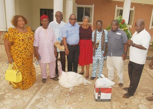 A GROUP PICTURE OF THE UCHEOGURU COMMUNITY REPRESENTATIVES / THE ADURE & ONYIMA OBIOHA FAMILY FOUNDATION WITH ITEMS DONATED TO THE FOUNDATION – A LIFE TURKEY/ CARTON OF WINE AND GARDEN EGG.
